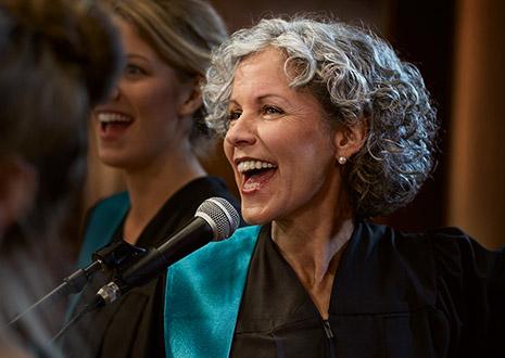 Fröhliche Frau singt im Chor.