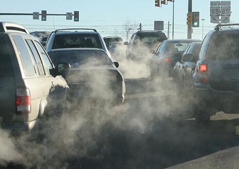 Autos stehen im Stau mit sichtbaren Auspuffgasen.