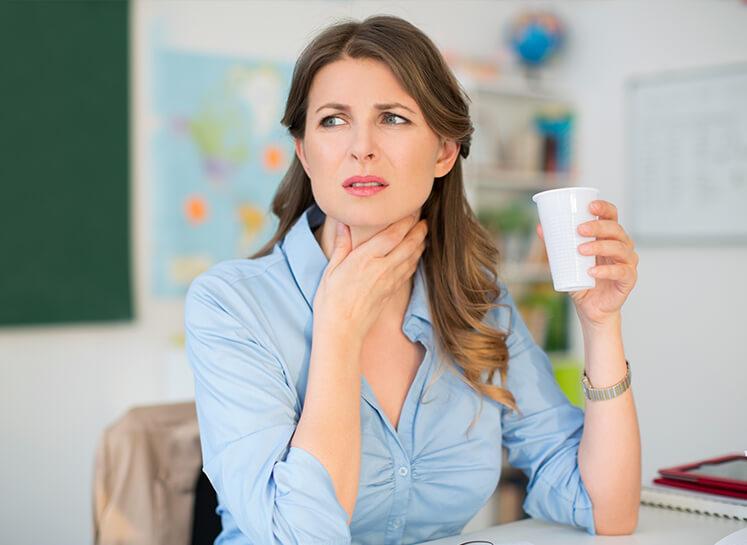 Frau mit Halschmerzen legt ihre Hand an den Hals.