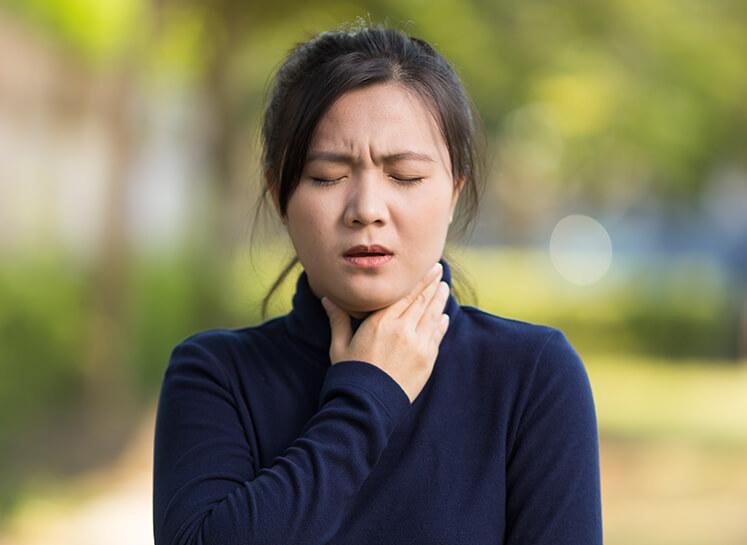 Junge Frau mit Heiserkeit berührt ihren Hals.